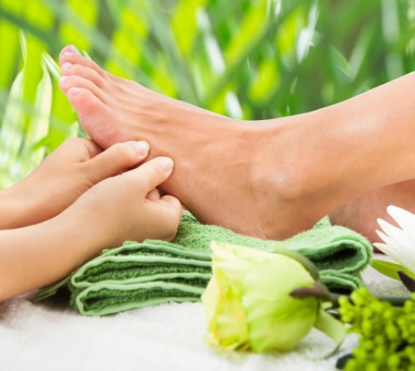 Cropped image of masseuse massaging woman's foot against leaves at beauty spa