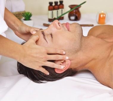Entspannter Mann im Day Spa bekommt eine Massage am Kopf